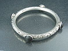 Sterling Silver Garnet Hallmarked Bangle Bracelet  Scrolled Sterling Silver 4 raised cabochon Garnets signed Sterling with another Hallmark Bangle Bracelet 2 1/2 inch inner diameter 3/8 inch wide. The 4 Cabochon Garnets are scratched (Priced accordingly)