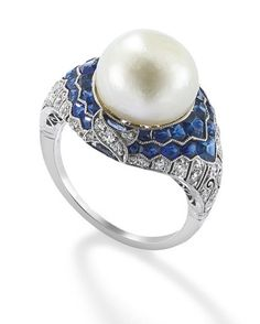 A natural pearl, diamond and sapphire art deco ring.  The central natural button pearl, measuring 11.51-11.71 × 9.08 mm, set within a calibrecut sapphire double cluster to a circular-cut diamond bezel and shoulders