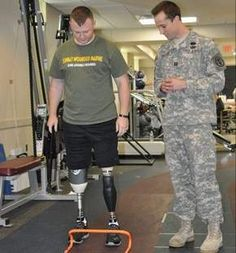 Army Capt. Bradley M. Ritland, physical therapist, observes Marine Cpl. Garrett J. Carnes walking over small hurdles during a physical therapy session in the Military Advanced Training Center (MATC) at Walter Reed National Military Medical Center on Friday.