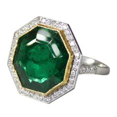 1950s Emerald Diamond Gold Platinum Ring | Platinum ring set with an octagonal-shaped emerald weighing approximately 8.50 carats, further set with round diamonds.