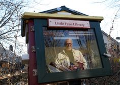 Rick Brooks, co-founder of the Little Free Library project, is reflected in the glass of Madison's first Little Free Library, which is on the east side bike path. Readers can simply take — or drop off — books from the little libraries set up in yards, parks and hospitals.