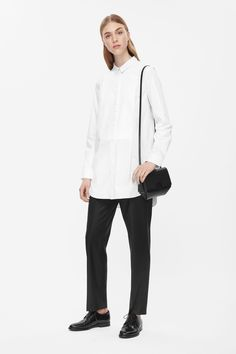 Made from crisp cotton with a contrast textured panel along the front, this long shirt has a graduated hemline. Fitted over the shoulders, it has a straight fit, a narrow pointed collar and partially hidden button fastening along the front