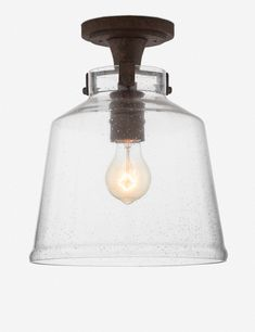 Taking a page from traditional style, this bronzed pendant features a bell-shaped glass shade, complete with bubbles and imperfections to add to the vintage-inspired look.