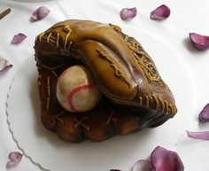 This cake baseball glove is covered in fondant. The ball is rice crispy treats with modeling chocolate. Entirely edible.