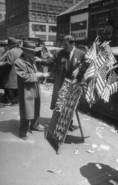 Vendor selling American flags & large 'I TOLD YOU SO' buttons amidst the gathering crowd in Times Square to celebrate the end of the war in Europe