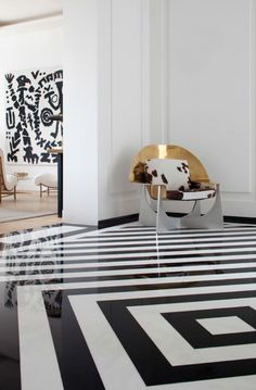 Pierre Yovanovitch: Black and white stripe floor and dramatic metal chair. Statement space.