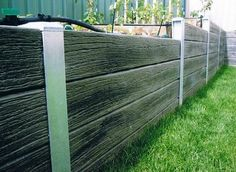 Steel and lumber retaining wall, modern design, reused elements.  For a fence? I think I know a guy that can help...