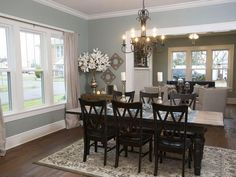 Love this dining room....timber floors, blue/green walls, black chairs, iron chandelier above table, doorway to sitting area.