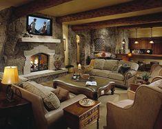 Rustic basement with fireplace and beams.  #basementdesigns homechanneltv.com