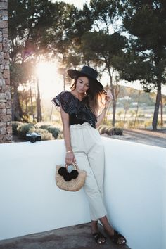 LOOK AT THE STARS - Lovely Pepa by Alexandra. Black one shoulder star print ruffles top+white high-rise cropped pants+black strappy flat sandals+black straw sun hat+raffia black pompom basket-bag+gold bracelet. Summer Casual Outfit 2017