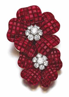 Ruby and diamond brooch, 'Deux Fleurs', Van Cleef & Arpels, 1996. Designed as two flowers, the petals composed of rubies en serti mystérieux, the pistils set with brilliant-cut diamonds, signed Van Cleef & Arpels, numbered, French assay and maker's marks, case stamped Van Cleef & Arpels. Sotheby's.