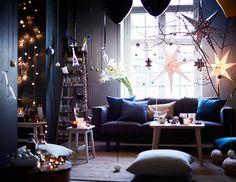 Séjour décoré avec des bougies allumées sur une table basse, une guirlande lumineuse au mur et trois grandes étoiles de Noël près de la fenêtre.