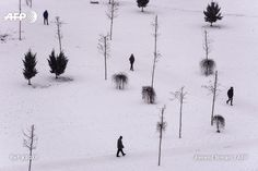 People walk through a snow covered park in Pristina on January 19, 2017, as the country continues to experience subzero temperatures. Armend NIMANI / AFP