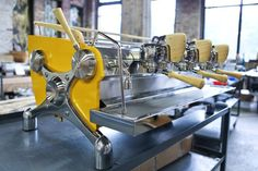 """""""Fratello Coffee Roasters & Analog Cafe custom yellow 3 group Slayer with polished X's, Bamboo Brew and Steam Actuators, Portafilter Handles and Cup Tray."""" (Facebook)"""