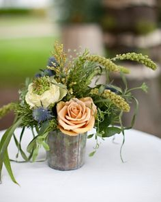 Florist Jack Lucky of Jack Lucky Floral Design composed arrangements of ivory and camel garden roses, green hydrangea, and wildflowers. These were placed in rustic pots.