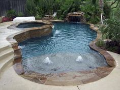 Pool with grotto, raised sitting area with stackstone facing, and beach entry with bubblers by elsie