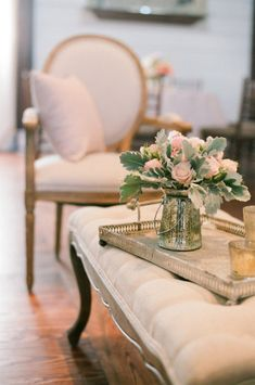 Soft peachy pink fresh flowers on a brass tray set on a lavish tufted ottoman adds the finishing touches to this elegant French room.