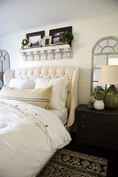 Neutral cottage master bedroom with salvaged corbel shelf above bed.