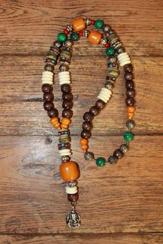 Necklace with brown wood beads, Tibetan silver spacers, White Yak bone rondelles,   bone beads, Malachite stone beads, red coral beads, Amber beads,& a ganesh amulet. 45 €
