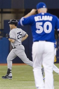 GAME 112: Friday, Aug. 10, 2012 - New York Yankees' Mark Teixeira, left, rounds the bases after hitting a solo home run off Toronto Blue Jays pitcher Steve Delabar (50) during eighth-inning baseball game action in Toronto.