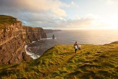 On the rugged Irish coast, Patch Wilson rambles out for an evening surf. Ireland. Photo: Chris Burkard