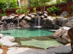 small natural looking pool with beach and waterfall