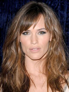 Jennifer Garner's smooth roots, side-swept bangs and soft waves give her tousled hairstyle barely-there movement.