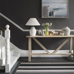 Add a sense of drama to a hallway with rich grey tones and contrasting bright white. Add a few personal touches through pretty accessories