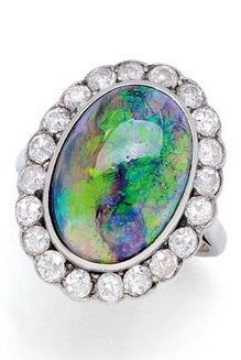 An Antique Crystal Black Opal and Diamond Ring, circa 1920. Centring an oval crystal black opal measuring 15.8 mm by 11.2 mm by 5.33 mm, surrounded by old mine-cut diamonds totalling approximately 1.20 carats, mounted in platinum and 18k white gold.