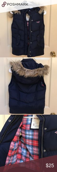 Hollister Puffer Vest Gently worn Hollister puffer vest in navy blue. Detachable hood with faux fur trim. Interior lines in warm plaid flannel material. Snap and zip closure in front. Hits at hip. Slight discoloration on collar as shown. Hollister Jackets & Coats Vests