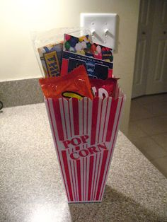 Read this great post about a gift idea for a movie buff. Popcorn container containing a gift card, popcorn and some candy.