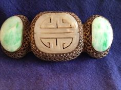Wonderful Chinese export buckle comprised of gilt silver filigree mount set with older carved jade cabs and focal stone.