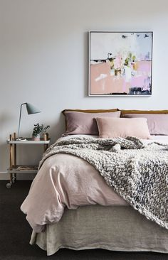 Dusty rose bedroom, with cozy chunky knit throw. Love the abstract art piece above the bed and the copper accents.