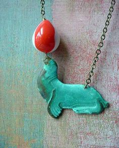 Sea Lion Pendant Circus Act Necklace Turquoise Patina Brass with Vintage Lucite Orange White Balancing Ball.  via Etsy.