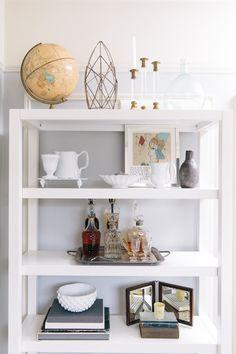 Create a mini bar: http://www.stylemepretty.com/living/2014/02/03/10-tricks-for-styling-your-bookshelves/