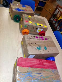 "PICASSO'S BASEMENT's Mexican painted buses. Ours were made out of upcycled boxes. Drilled a hole into orange juice caps, put dowels through the boxes, stuck on the caps and secured them with a small ""tip"" of duct tape. Then we painted them. The wheels really turned!"