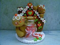 A whimsical gingerbread pair and their gingerbread house. The little fellow in the forefront is holding a candy jar full of candy canes! (Also included is a lollipop)!  This is an original design thats been handcrafted from polymer clay. The piece stands approximately 3 tall and all parts have been secured with liquid polymer for increased strength.   Not a toy...not suitable for young children.