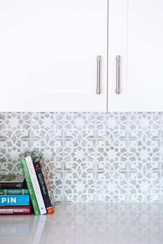 A graphic gray and white tile backsplash is the perfect complement for the crisp white cabinets and solid white countertops in this updated kitchen by Pure Design Interiors.