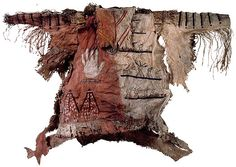 "Mandan Man`s Shirt (ca.1830) Material: Hide, rabbit skin, porcupine quills, sinew, beads, human hair, pigment. Lent by the Department of Anthropology, Smithsonian Institution. Catlin acquired his sitters' clothing to exhibit in the Indian Gallery as proof of the accuracy of his art. His greatest prize was a shirt given to him by the Mandan chief Four Bears, ""with the history of his battles emblazoned on it."" The shirt seen here resembles the one worn by …"