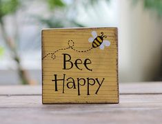 Bee Happy Small Wood Sign Display this hand painted shelf sitter sign on a wall, shelf, or office desk to remind others (and yourself!) to smile, and choose happy! With its tiny hand painted bumblebee, this little sign makes a unique and happy spot of spr Wood Block Crafts, Wooden Crafts, Wood Blocks, Glass Blocks, Wooden Diy, Primitive Wood Signs, Wooden Signs, Painted Wood Signs, Bee Crafts