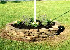 Simple rock circle flower bed around flag pole Flag Pole Landscaping, Landscaping With Rocks, Eagle Project, Raised Garden Beds, Flower Beds, Backyard Ideas, Garden Ideas, Front Yards, Landscape