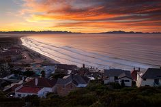 Muizenberg  Calm surf rolls ashore on Muizenberg beach as beautiful dawn light colours the clouds over the Cape Mountains