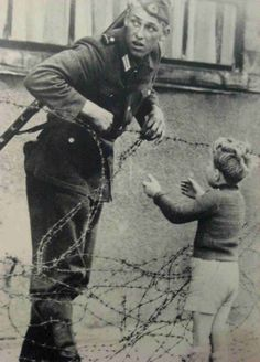 16.) An East German soldier helps a little boy escape to his family in the west.