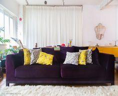 Sala de estar integrada com sofá roxo e almofadas amarelas estampadas.