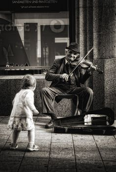 ZsaZsa Bellagio. Street musician performs while a child dances. Black and white photograph. #photography #Black #Photography