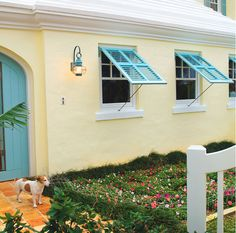 The turquiose shade of these Bermuda shutters was custom matched to make this warm façade come alive with pops of cool color. Bermuda shutters are perfect for shade, breeze, and privacy. Exterior Door Colors, Exterior Front Doors, House Paint Exterior, Exterior Design, Exterior Siding, Window Shutters Exterior, Window Awnings, Garage Doors, Bermuda Shutters