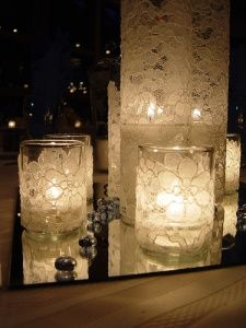 """cylinder vases (8"""", 10"""", and 12"""" tall) wrapped in lace surrounded by votives with floating candles in water"""