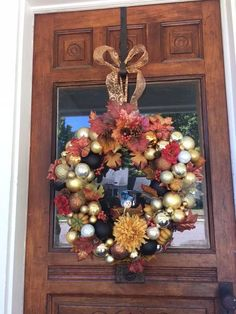Fall wreath created with orange, gold, black and cream bulbs. Topped with a variety of fall leaves, acrons, pine cones and fall flowers. Peaking its head out of the bottom of the wreath is a scarecrow wearing a blue hat. This wreath hangs by a beautiful orange and cream bow that