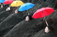 Sand Bath in Beppu, Japan where bathers can enjoy the volcanic hot springs and be buried in the black heated sand to their necks. Note the sun protection! A sand bath runs about 1000 Yen. http://tinyurl.com/3qqgw8f #Beppu #Japan #Sand_Bath