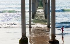 Child playing under the pier with the waves lapping at her feet.